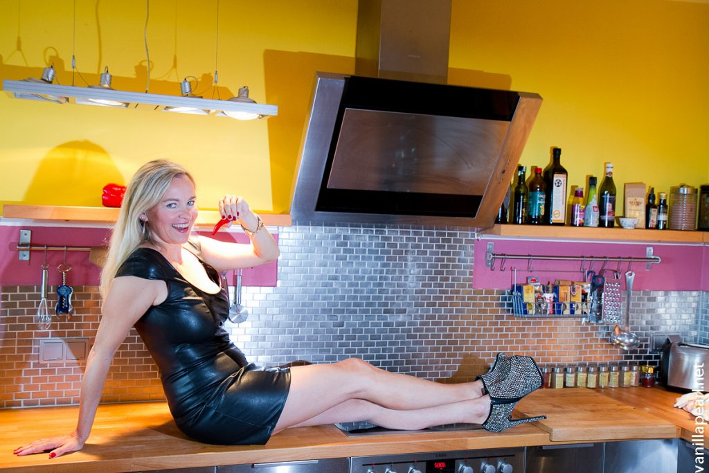 Chrstina VanillaPearl wearing black vinyl dress - magic cooking in the kitchen - enchanting table for magic food