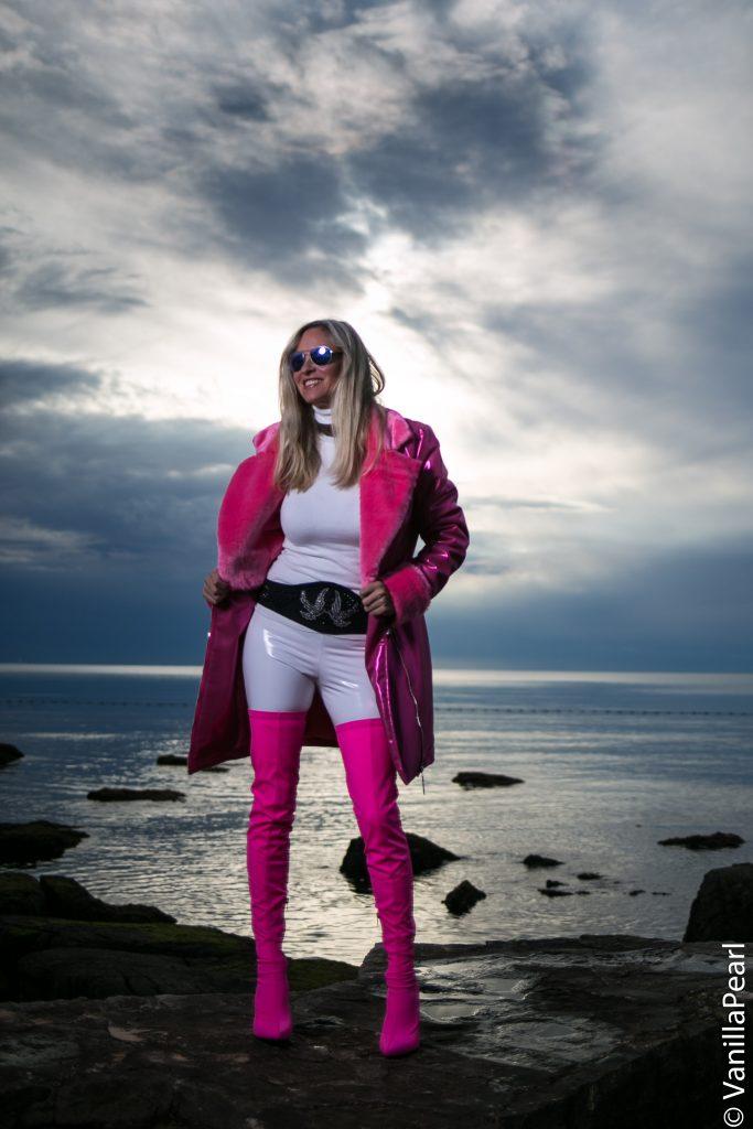 Christina, VanillaPearl und Arcanum Designerin in Arcanum Fellmantel Crystal Pink OTKB und weißer Lackleggings am Meer