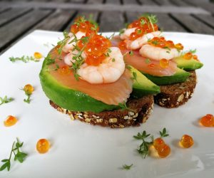 Shrimps on salmon on avocado